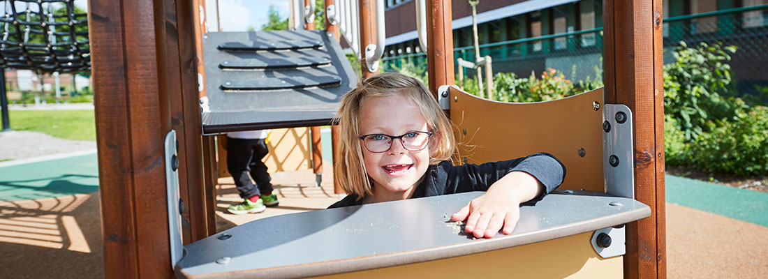 Girl playing shop on an inclusive playground multi-play unit
